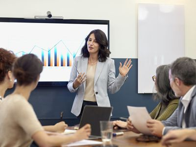 Woman leading a meeting with other people at a conference table with chart on wall behind her.