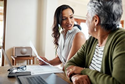 Cropped shot of an attractive young woman sitting and explaining financial documents to her grandmother in their home