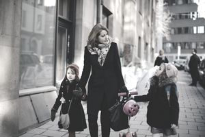 Mother talking to daughter while walking on sidewalk in city during winter