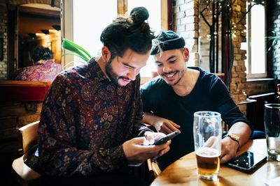Two men drinking together and looking at a smartphone at a craft-beer bar