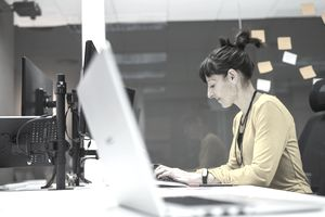 person in yellow sweater working on computer at desk