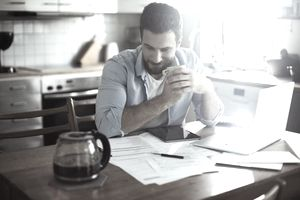 A man sits with his elbows resting on a kitchen table, which is bestrewn with papers, a calculator, and open laptop; he clutches a cup of coffee and grins slightly at the good news that debt relief is near at hand.