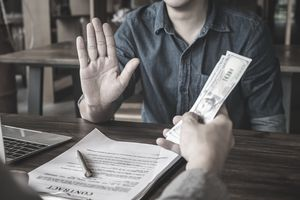 A man in a holds up his palm to reject an offer of cash with a contract and pen laying on the table in front of him.