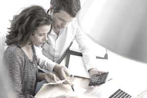 Couple implementing a budget plan using a calculator and laptop