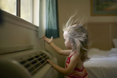 Toddler uses her hand to play with the air coming from a room air conditioner as it blows the hair away from her face