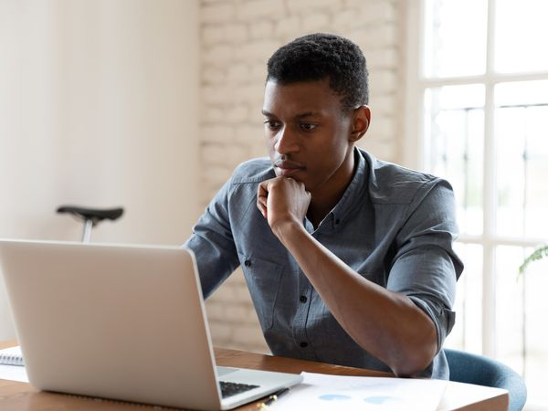 young adult in jean shirt working on laptop
