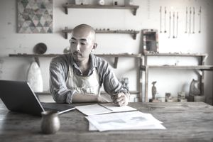 a man working on a laptop and writing in a ledger