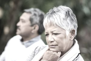A woman leans her chin against her fist and contemplates divorce with her husband in the background.
