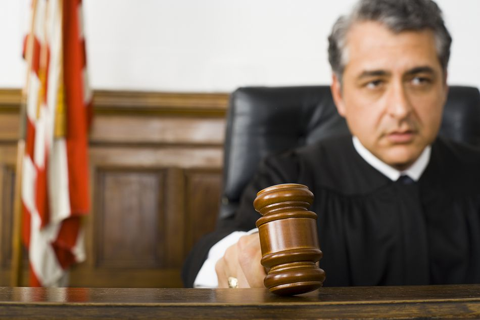 A male judge hitting a gavel on the bench