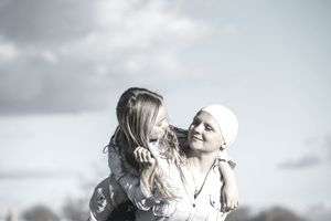 A woman with a bandana on her head gives her daughter a piggy-back ride