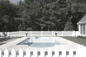 Backyard swimming pool surrounded by a white picket fence