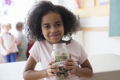 young girl holding a clear glass jar of money with a label showing the word