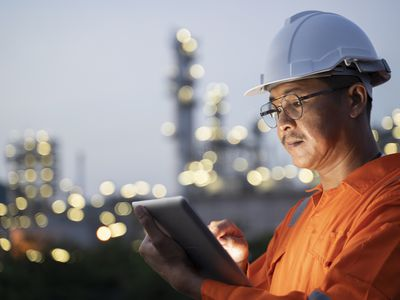 An oil worker checks production data during a shift.