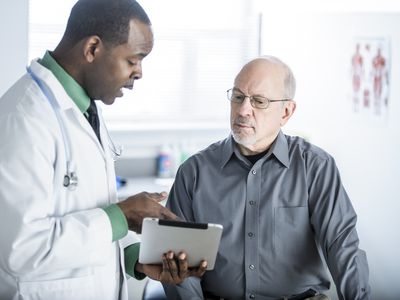 Doctor with digital tablet talks to patient in exam room