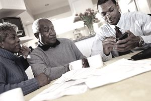 An older Black couple work with a tax professional to add to tax-advantaged funds.