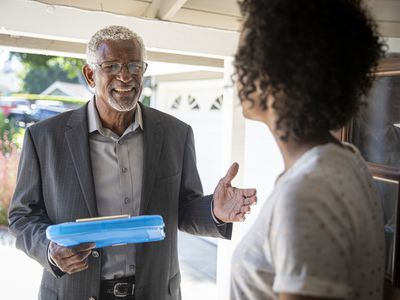 A woman greets a smiling man at her front door.