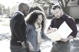 Two homeowner clients looking at a folder with a salesman on the street in a residential block.