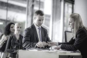 Man signing paperwork with a teller at a retail bank