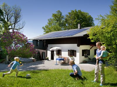 family playing outside in front of their home that has a solar panel system