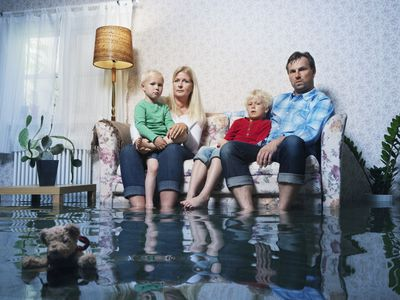 Family sitting on couch in flooded living room looking concerned