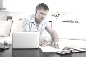 A man reviews business papers by a laptop