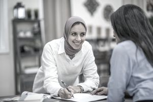 Two Muslim women are working in their home office. They are having a meeting. One woman wearing a head scarf is writing in a notebook.