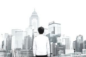 Man looking out over cityscape of financial district in China