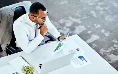 Cropped shot of a handsome young businessman sitting in his office and looking contemplative while reading paperwork