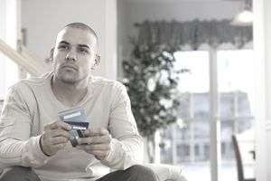 a man holding three credit cards looking thoughtful
