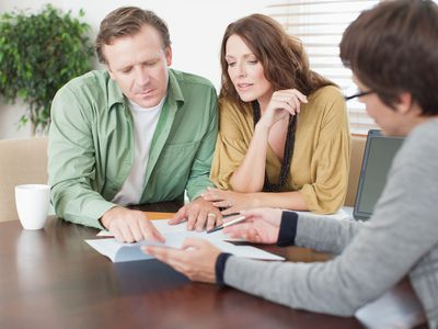A couple reviews financial paperwork with an advisor.