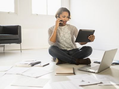 Black businesswoman using cell phone and digital tablet on floor