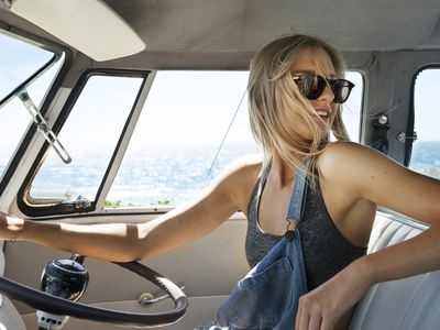 A woman in sunglasses drives in a car and looks backward