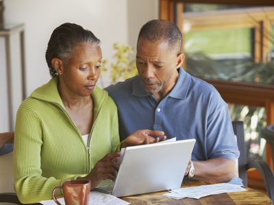 Couple looking distressed as they review bills together