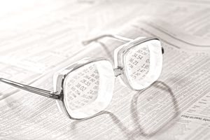 A pair of glasses sitting on the financial section of a newspaper