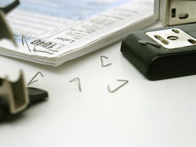 Tax form with stapler, staples and staple remover, close-up