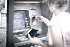 An older woman inserting her debit card into an ATM