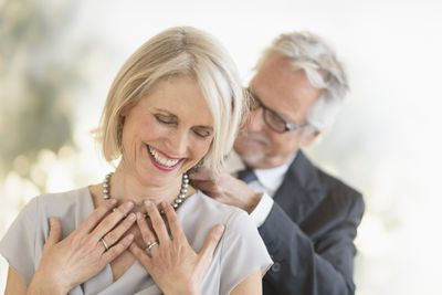 Senior couple, as man puts necklace on woman