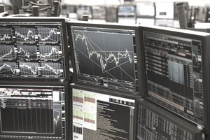 Arrangement of computer monitors showing stock market movements.