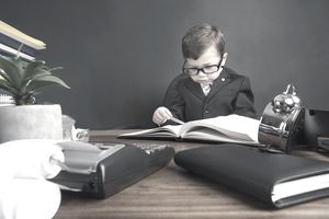 Young boy in suit working at desk with books and adding machine