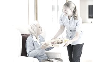 Woman helping an old lady to reduce her assisted living costs.