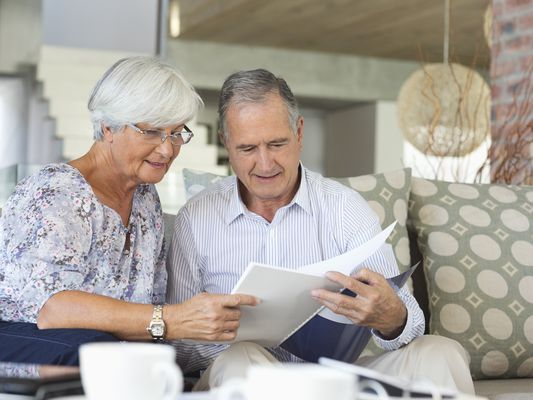 Senior couple reading over a retirement plan while sitting on their couch