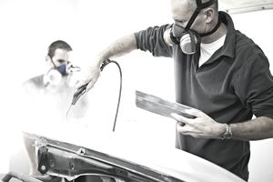 Man blowing dust from front quarter panel of car