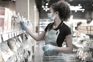 One young supermarket employee sorting products on the shelfs