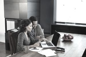 A young couple using a laptop and paying off credit card debt