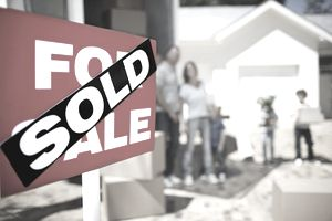 Sold Sign on House With Family in the Background