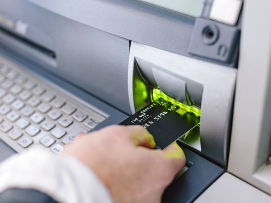 Close up of womans hand inserting credit card into cash machine