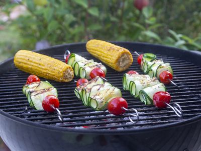 Skewers of vegetables and corn cobs cooking on outdoor grill