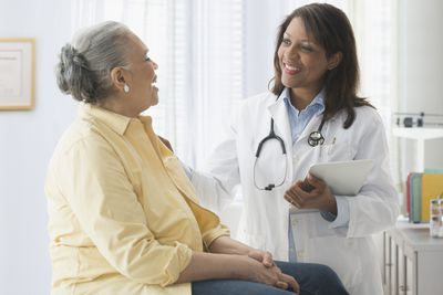 Senior woman talking to doctor in office