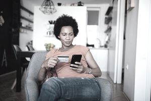 Woman holding credit card while looking at smartphone