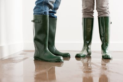 couple in boots hope homeowner insurance covers the water damage in flooded home